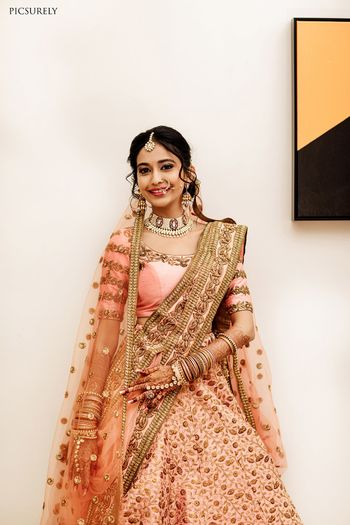 A bride in pink lehenga and scalloped dupatta