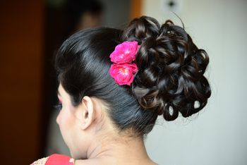 Photo of Wavy Hair Bun with Pink Flowers in Hair