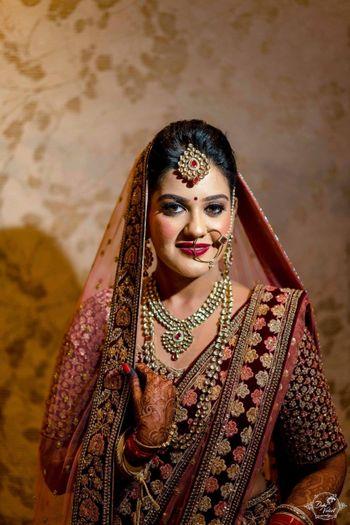 Bride with heavy blush in maroon winter lehenga