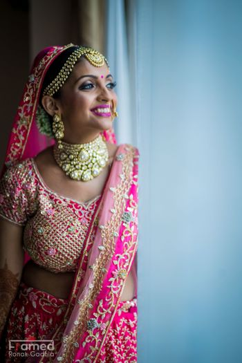 Happy bride in bright pink lehenga