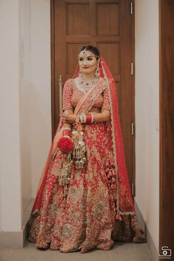 Bride in red and gold embroidered lehenga