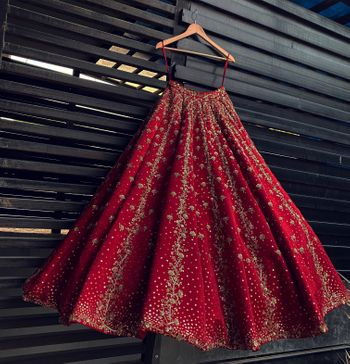 Photo of Red lehenga hanging on a hanger.