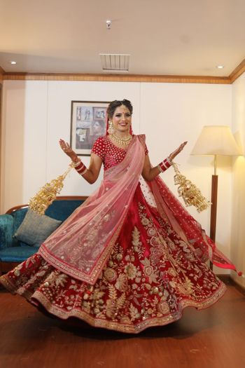 Twirling bride in red velvet lehenga
