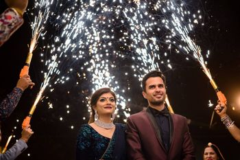 Photo of Guests holding cold pyros for bride and groom entry