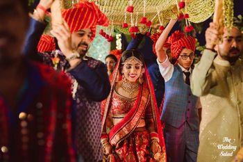 Bride in red entering under gold phoolon ki chadar