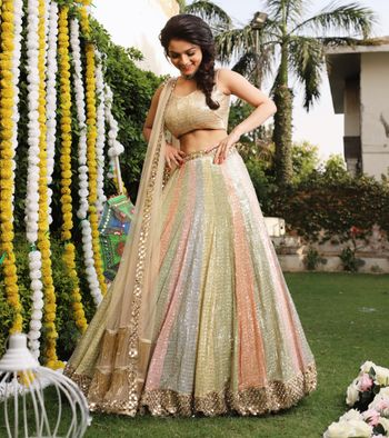 A bride to be in a sorbet-colored outfit for her mehndi