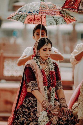 Bride entering under traditional umbrella