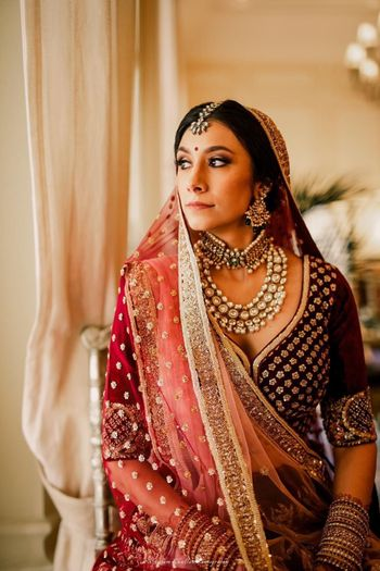 Bride in layered choker and maroon lehenga