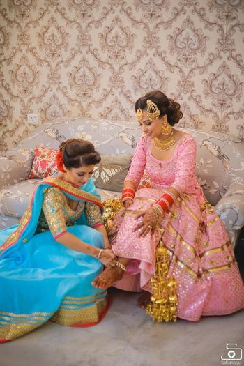 Bride with sister helping her with anklet