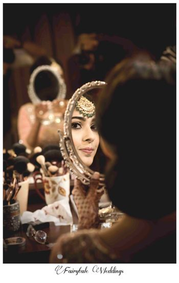Photo of bride looking in the mirror