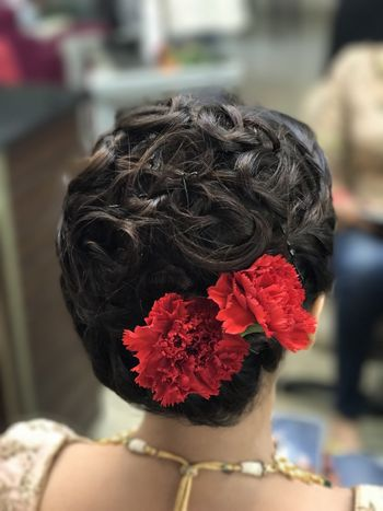 Curly bun with red carnations for bride