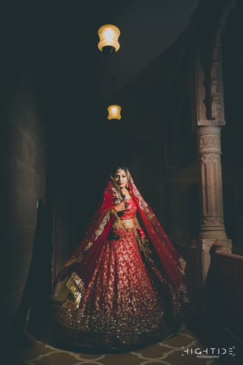 Twirling bride in red and gold sequin work lehenga