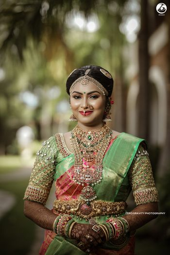 Pretty south Indian bride with a light kanjivaram saree and jewels for her wedding