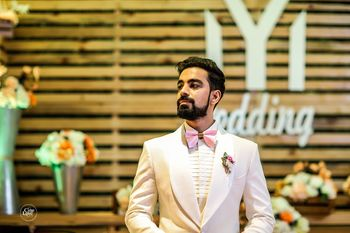 Quirky groom with light pink bow tie white suit