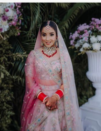 Bridal portrait with light pink lehenga and blue embroidery with ombre dupatta