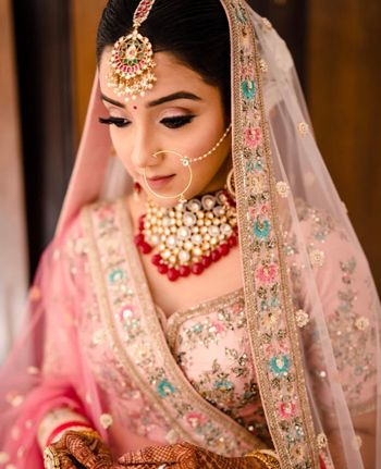 Bride in pink lehenga with red jewellery