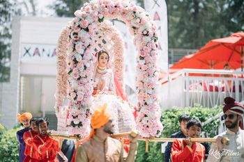 Photo of Bride in floral Palki entry shot