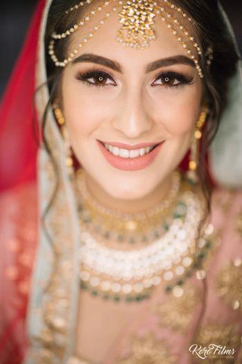 Subtle bridal makeup with peach lips