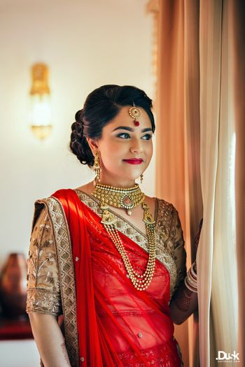 Photo of Red and Gold Lehenga Bride with Gold Maangtikka