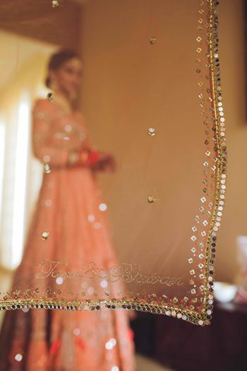 Bridal lehenga in peach with names of the couple