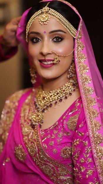 Subtle smokey eye makeup for a bride dressed in fuschia pink lehenga