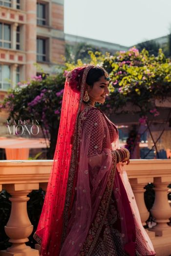 A bride in a red lehenga and flowers in her hair