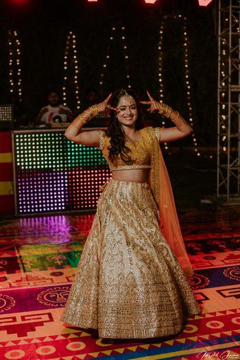 Dancing bride in dull gold lehenga