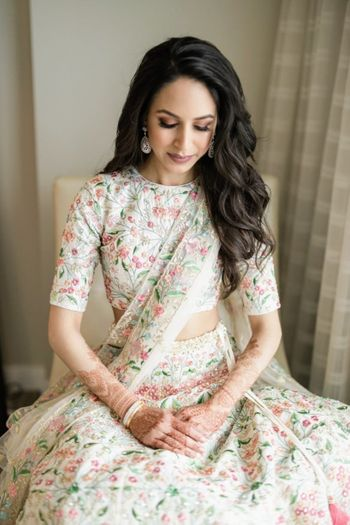 Bride dressed in an ivory lehenga with elegant thread work.