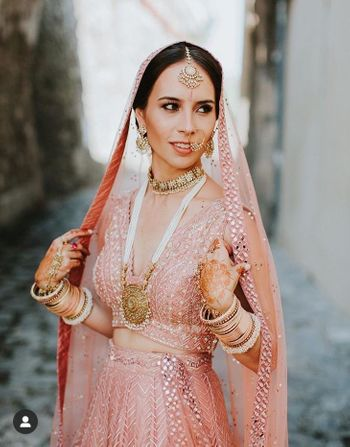 Photo of Bride wearing a pastel pink lehenga with statement haar.