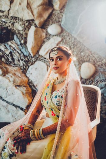 Bride dressed in an ivory lehenga with peach and yellow dupattas.