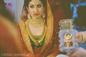 Photo of bride looking through the mirror shot