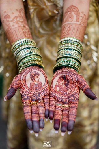 Mehendi design with bride and groom portraits on each hand