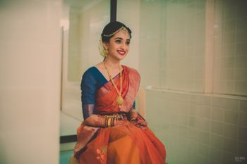 Photo of South Indian Bride in Orange and Peacock Blue Saree
