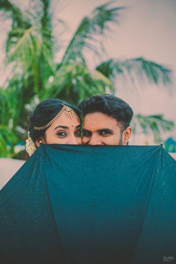Photo of Couple Behind The Umbrella Fun Shot