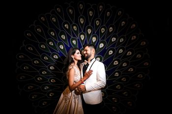 Sangeet couple shot against peacock backdrop