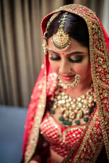 Photo of Bride in red lehenga contrasting jewellery