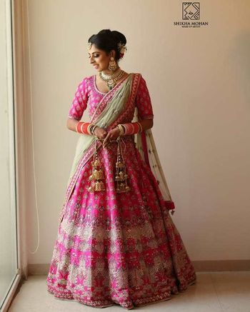 A bride in a pink lehenga with a contrasting mint dupatta