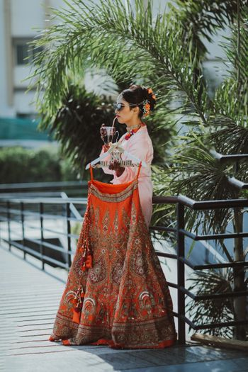 Bride holding lehenga and having a drink