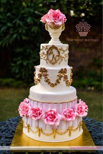 Photo of multi story white and gold wedding cake