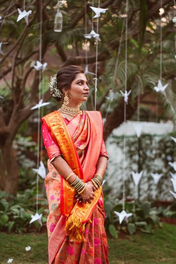 Bride in orange saree against paper decor