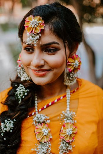 A bride to be in dry floral jewelry for her mehndi