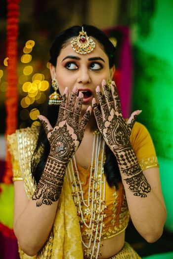 Bride showing off her mehendi with a surprised expression