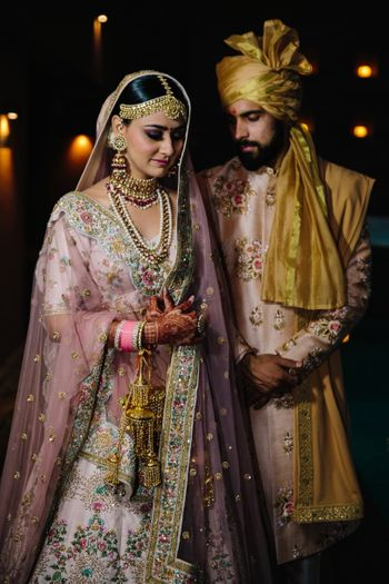 Bride and groom in light pink outfits with contrasting safa