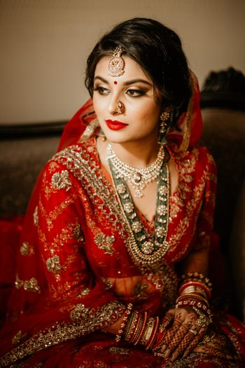 Bridal makeup with red lips and green jewellery