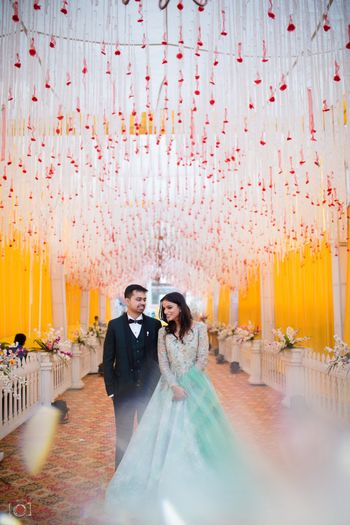 Engagement or sangeet couple shot with floral string decor