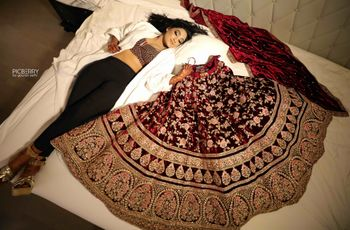 Bride on bed with maroon bridal lehenga