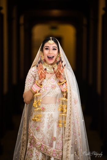 Happy and excited bride in white lehenga shot