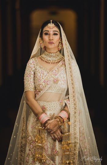 Pouting bride in ivory lehenga