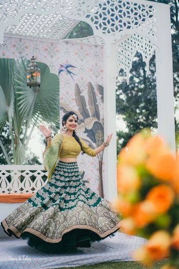 Bride twirling wearing green mehendi lehenga