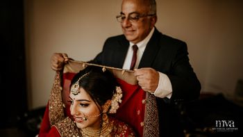 Bride with father placing dupatta on her head